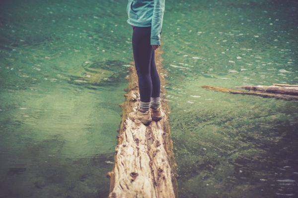 Woman in hiking boots by water - HelloTrail